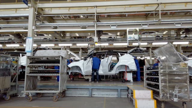 factory workers assembling car on production line - manufacturing machinery stock videos & royalty-free footage