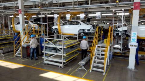 vídeos y material grabado en eventos de stock de factory workers assembling car on production line - vehículo eléctrico