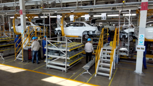 vídeos de stock e filmes b-roll de factory workers assembling car on production line - chassi