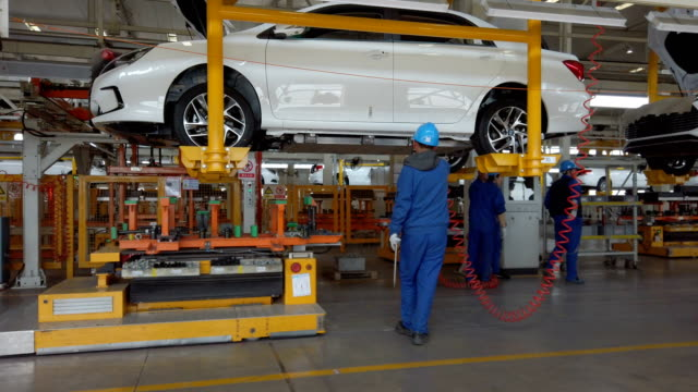 factory workers assembling car on production line - electric vehicle stock videos & royalty-free footage