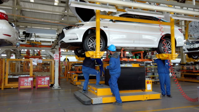 factory workers assembling car on production line - 自動車産業点の映像素材/bロール