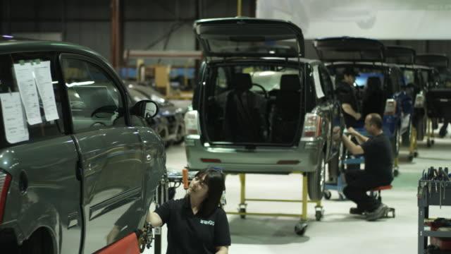 vídeos de stock, filmes e b-roll de ws factory workers assembling electric cars on production line, st. jerome, quebec, canada - indústria automobilística