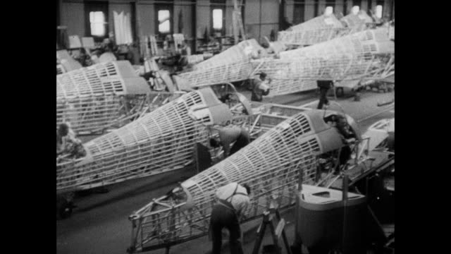 montage factory workers assembling hurricane fighters, including swinging down the engine and rolling tires / united kingdom - seconda guerra mondiale video stock e b–roll