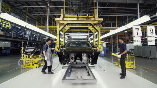 ws factory workers attaching hoist to car on assembly production line / samut prakan, bang muang mai, thailand - car plant stock videos & royalty-free footage