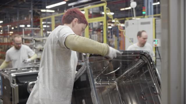 vidéos et rushes de ouvriers de l'usine vérification des produits finis de moitié à leur poste de travail - slovénie