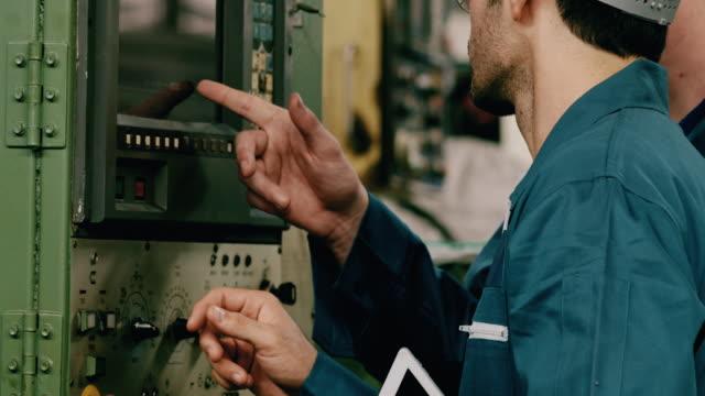 vidéos et rushes de ouvriers d'usine discutant le travail utilisant la tablette et pointant à pannel dans la ligne d'usine. moyen-orient et ethnie caucasienne. concept de fabrication. - manufacturing occupation