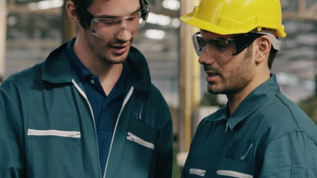 vidéos et rushes de ouvriers d'usine discutant le travail utilisant la tablette dans la ligne d'usine. moyen-orient et ethnie caucasienne. concept de fabrication. - manufacturing occupation