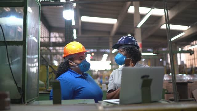 非公式な会議を行い、ラップトップ上の情報を分析する工場労働者 - 操作する点の映像素材/bロール