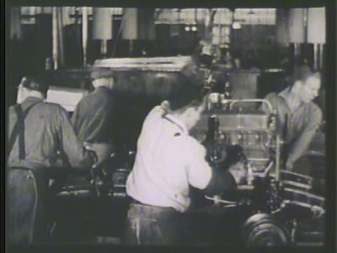 factory workers fitting engine into car on assembly line male attaching steering wheel column vs tires hanging from convey belt fitting wheels onto... - 1935 stock videos & royalty-free footage