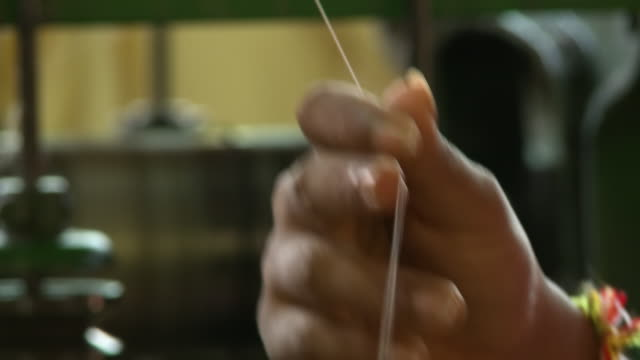 factory worker's hand working on a silk thread - silk stock videos & royalty-free footage