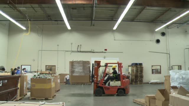 factory workers in an industrial facility in la processing electronics moving things with forklift - e waste stock videos & royalty-free footage