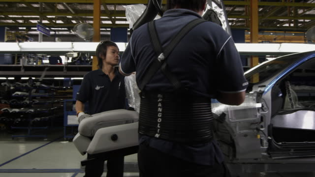 ms pan factory workers installing car seat on production line / samut prakan, bang muang mai, thailand - 自動車工場点の映像素材/bロール