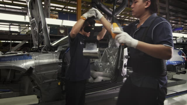 MS ZI Factory workers installing car seat on production line / Samut Prakan, Bang Muang Mai, Thailand
