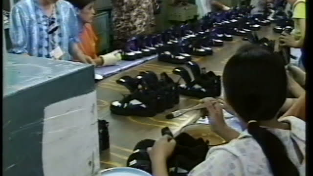 ZI Factory workers on a Nike assembly line as shoes are moving slowly along / Shanghai China