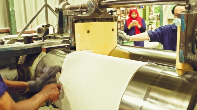 stockvideo's en b-roll-footage met fabrieksarbeiders die hoge snelheid industriële machine - productielijn werker
