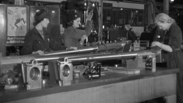 MONTAGE Factory workers operating various machines inside an armament factory / United Kingdom