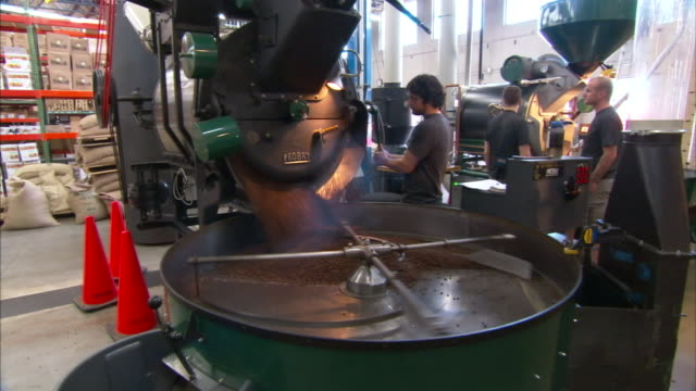 factory workers oversee the dumping of coffee beans into a vat. - rühren stock-videos und b-roll-filmmaterial