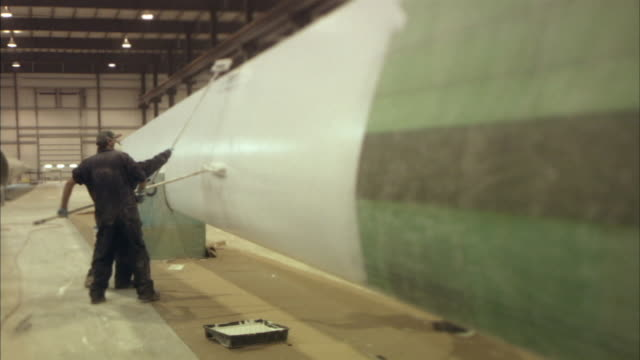 MS Factory workers painting large part of wind turbine with rollers/ Pipestone, Minnesota