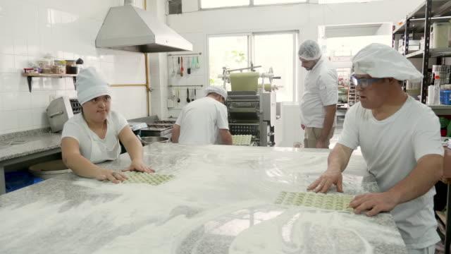 fabrikarbeiter bereiten pasta-formen zu raviolis zu machen - haarnetz stock-videos und b-roll-filmmaterial