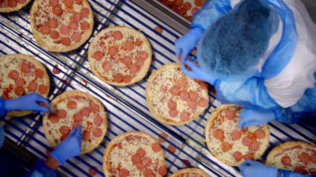factory workers put pepperoni on pizzas - fabrik stock-videos und b-roll-filmmaterial