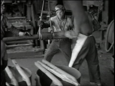 b/w factory workers slamming pole against surface - 1920 stock videos & royalty-free footage