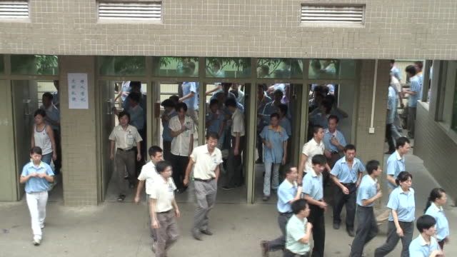 vidéos et rushes de ha ms zo factory workers swiping id cards and leaving through doorway/ dongguan, china - suivre activité avec mouvement