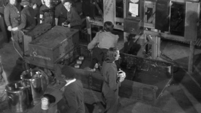 montage factory workers taking a break from operating machinery to get snacks and a drink from vendors, worker feeding milk to a cat / united kingdom - 1940 stock videos & royalty-free footage
