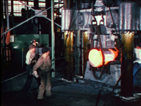 1946 factory workers using poles to position molten cylinder in machine in factory / industrial - 1946 bildbanksvideor och videomaterial från bakom kulisserna