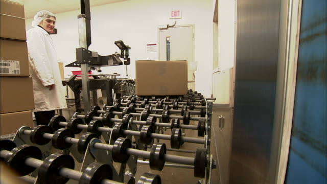 vidéos et rushes de ms factory workers watching as boxes roll off conveyor belt and onto rollers/ new jersey - charlotte médicale ou sanitaire