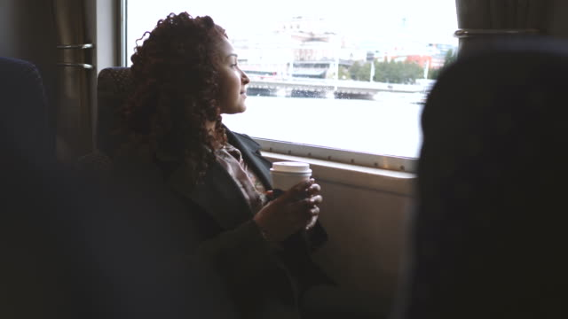 Fade in shot of businesswoman holding disposable coffee cup while looking through ferry window