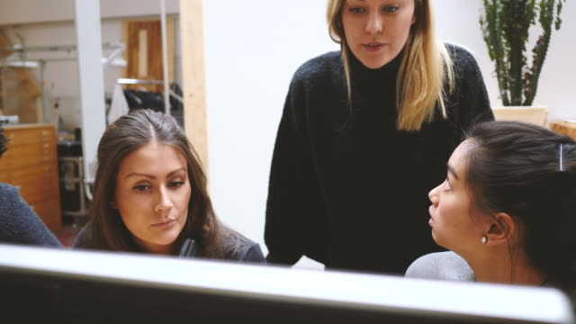 fade in shot of confident young businesswomen discussing strategy over desktop pc in new office - fade in stock videos & royalty-free footage