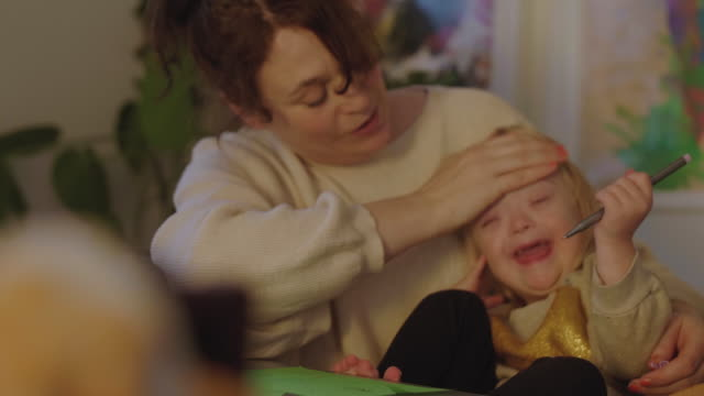 fade in shot of mother embracing disabled daughter while sitting by table - fade in stock videos & royalty-free footage