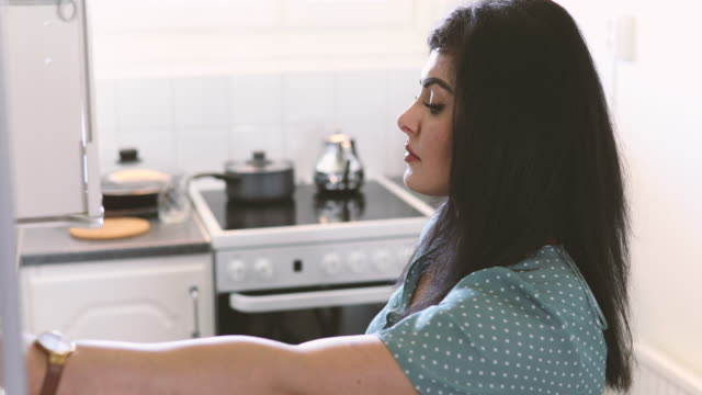 fade in shot of woman with roasted bread turning on button of automatic cabinet in kitchen at home - fade in stock videos & royalty-free footage