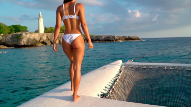 vídeos de stock, filmes e b-roll de fade in shot of young female tourist walking on catamaran in sea, woman in bikini enjoying summer on boat near lighthouse - montego bay, jamaica - swimwear