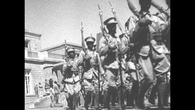 fade in ls of troops parading past imperial palace / vs dissolves of soldiers marching / mls emperor haile selassie and commanders standing on... - black and white stock videos & royalty-free footage