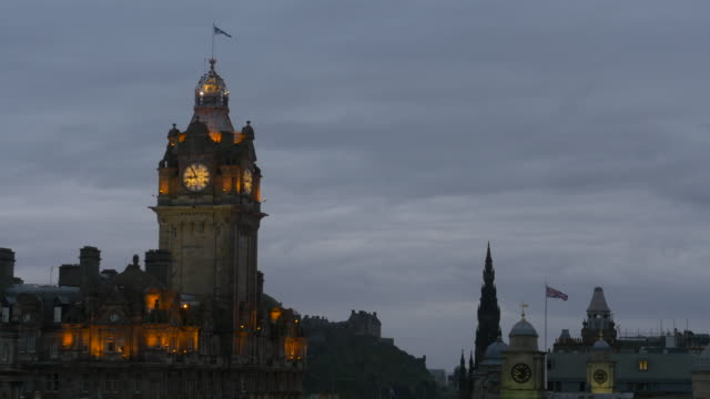 T/L MS Fading light at dusk in Edinburgh, Scotland, lighted clock tower of Balmoral Hotel at Waverley Station in foreground, Scott Monument and Edinburgh Castle in Old Town Edinburgh also visible.