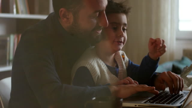 fahter is showing his boy things on a laptop - middle east stock videos & royalty-free footage