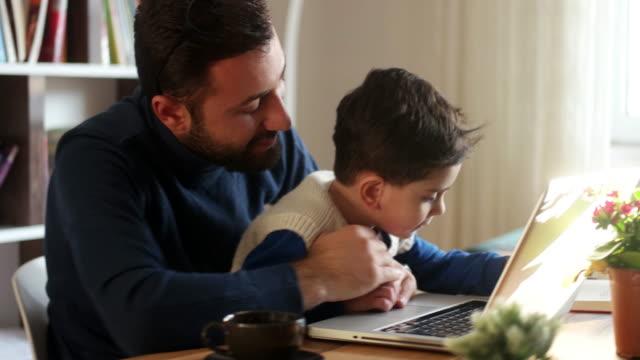 vídeos de stock, filmes e b-roll de fahter está mostrando coisas para seu filho em um laptop. - oriente médio etnia