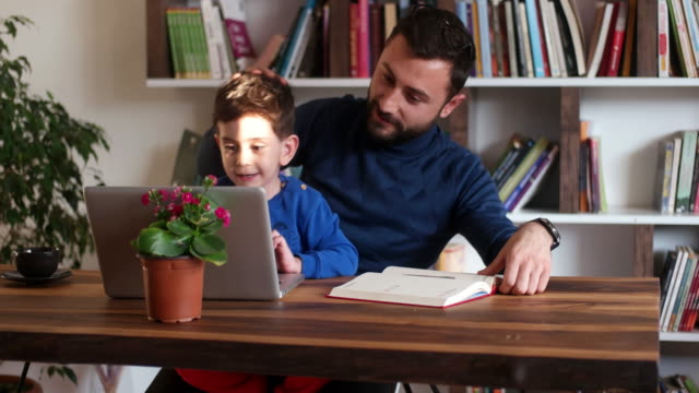 fahter is showing his boy things on a laptop - father stock videos & royalty-free footage