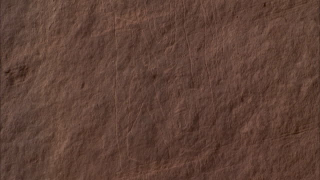 Faint drawings carved into the sandstone wall of a neolithic copper mine. Available in HD