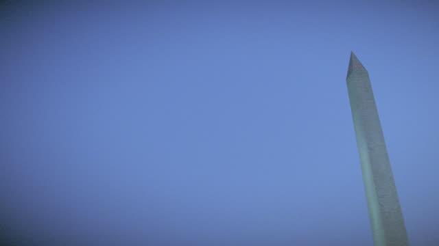 faint lights illuminate the washington monument at golden hour. - golden hour stock videos & royalty-free footage
