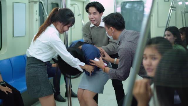 vídeos y material grabado en eventos de stock de mujer desmayada ayudada por los pasajeros en el tren del metro - mareado