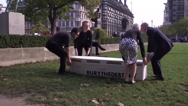Fair Funerals campaigners carry a mock coffin across Parliament Square during a protest calling on the government to increase the state fund to cover...