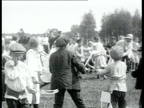 fair in mytishchi organized by the local peasant's soviet: in summer, brass band and people arrive in big empty field, children play, dance, vs... - anno 1920 video stock e b–roll