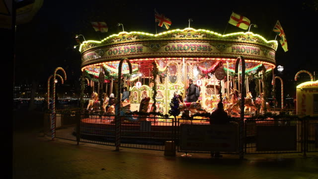 fairground carousel is seen on the south bank on december 7, 2016 in london, england. london is now lit up and ready for christmas, with festive... - roundabout stock videos & royalty-free footage