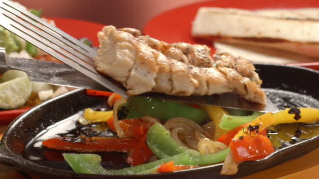 CU fajita pan with sizzling oil frying sliced bell peppers and onions as slices of seared chicken breast are laid over the veggies with spatula