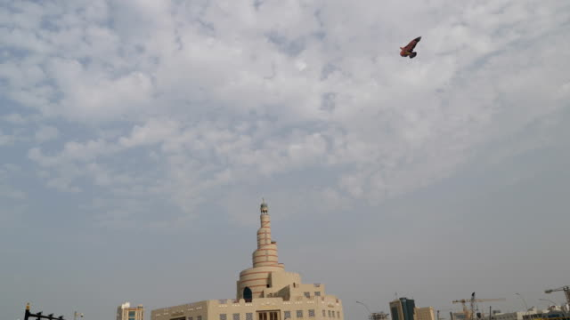 A falcon dragon flies over the minaret of the mosque in Doha 4K resolution