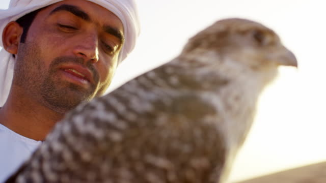 Falcon tethered to male owner wearing Arabic dress