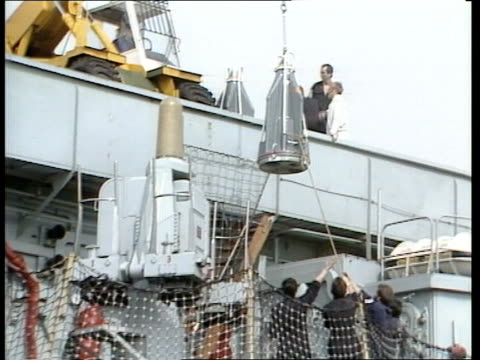 """task force; portsmouth: hms """"invincible"""" tilt down boxes up l-r on conveyorcms hand in protective glove signalsditto as generator up in... - hand on heart stock videos & royalty-free footage"""
