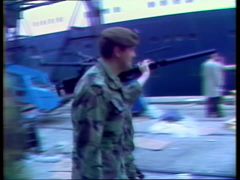troops leave on qe ii england s'hampton docks ms lorry and coach with welsh guards arriving lr day ms army lorries lr ms welsh guards band playing on... - フォークランド諸島点の映像素材/bロール